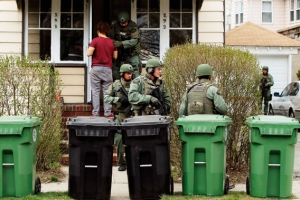Residents watch as police officers search house to house for the second suspect in the Boston Marathon bombings in a neighborhood of Watertown